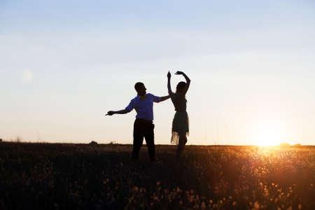 chicas bailando: Siluetas Pareja joven bailando en el campo al atardecer Foto de archivo