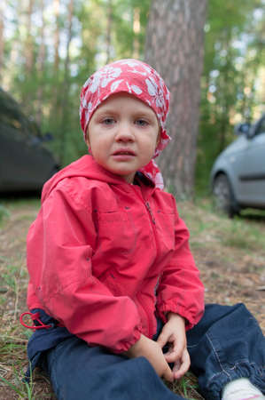 Crying little girl sitting on the ground in forest  photo