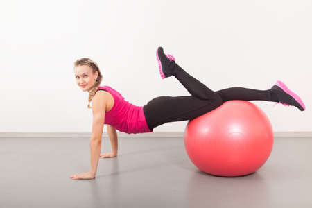 Athletic young woman with red ball on the floor  photo