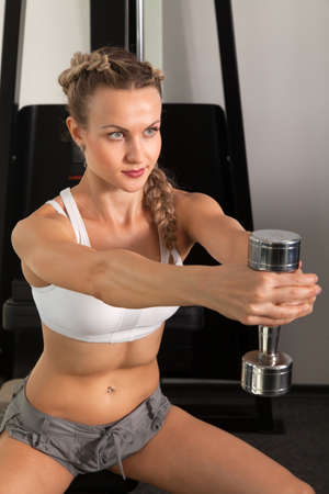 Athletic young woman with dumbbell in the gym  photo