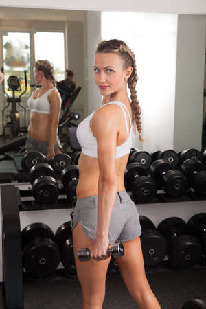 Athletic young woman with dumbbells in the gym  photo