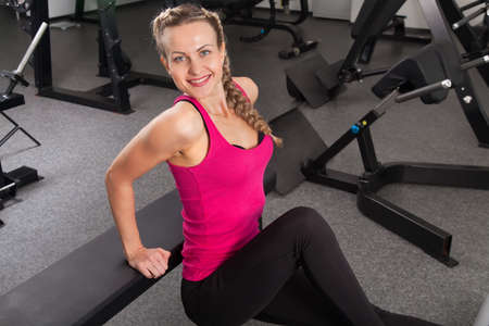 Athletic young woman training on exerciser in the gym  photo