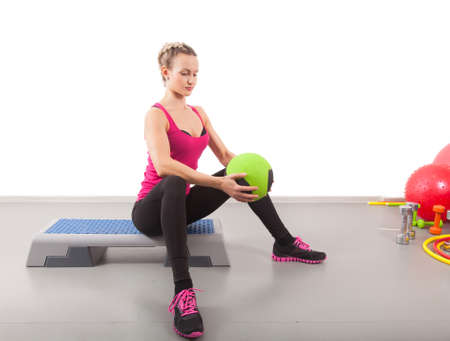 Athletic young woman training with green ball in the gym  photo