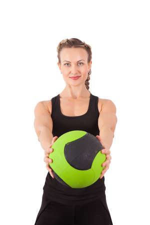 Athletic young woman training with green ball isolated on white