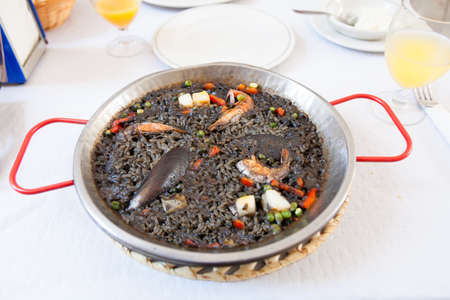 Paella negra on the pan, white table and glasses with juice Stockfoto