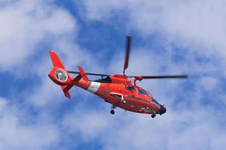 Red rescue helicopter moving in blue sky with blur propeller Stockfoto