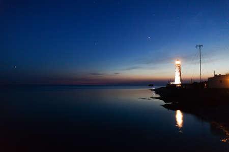 Lighthouse on the water edge near sea at night Stockfoto