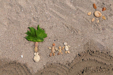 three palm trees: Happy family and palm tree made from stone on the sand beach  Stock Photo
