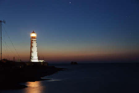 Lighthouse on the water edge near sea at night  photo