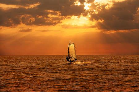 windsurf: Windsurfista navegando en el mar al atardecer