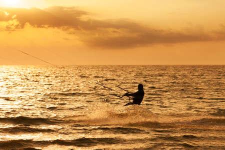 Kite surfer springt uit het water bij zonsondergang oceaan