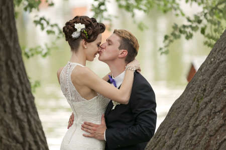 Just married couple kissing between tree trunks and pond