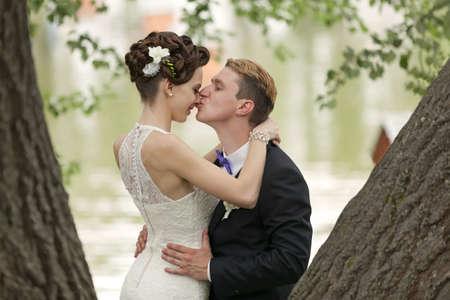 Net getrouwd paar zoenen tussen boomstammen en vijver Stockfoto - 20829449