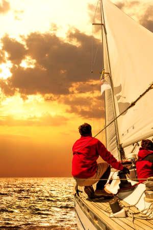 marinero: La gente en el barco de vela en el mar al atardecer