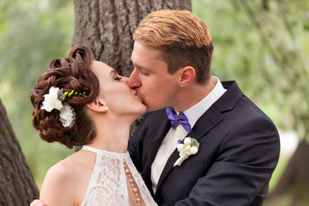 young couple kiss: Just married couple kissing between tree trunks and pond