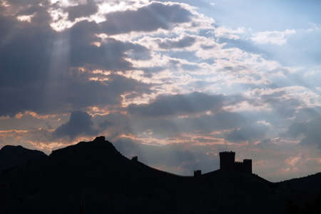 genoese: Genoese fortress silhouette with blue sky and clouds at sunset