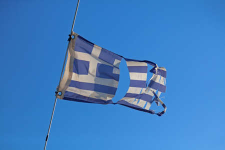 demolished: Torn greece flag waving on the wind  Stock Photo