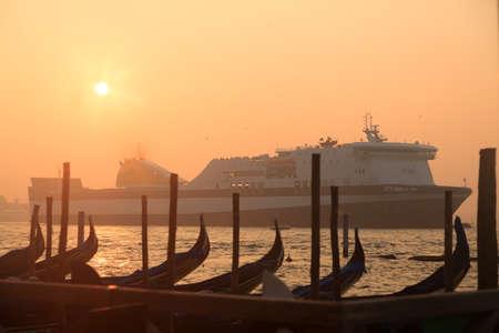 ferrying: Ferryboat sailing near venetian gondolas at sunrise
