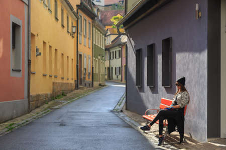 Teenage girl sitting on the bench on old city street Bamberg, Germany Stockfoto