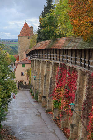 der: Rothenburg on Tauber castle wall and tower with autumn vines and trees