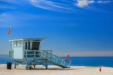 olas de mar: Estaci�n del salvavidas con la bandera americana en la playa Hermosa, California, EE.UU. Foto de archivo