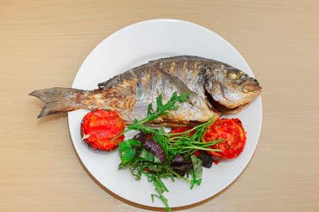 plato de pescado: Pez dorado a la parrilla con tomate, rúcula y albahaca en la placa blanca y mesa de madera