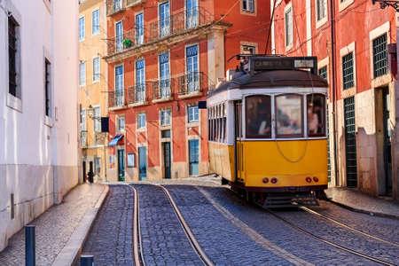 Vintage Lisbon tram on city street, sunny day, Portugal Editorial