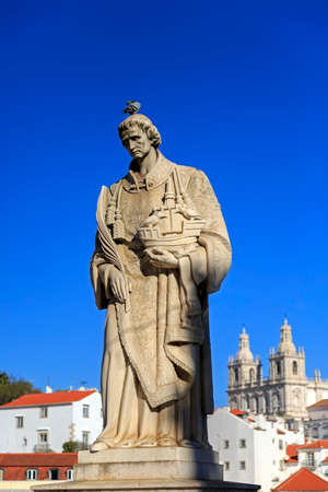 statue: Statue of Saint Vicente de Fora in Lisbon and house roofs, Portugal Stock Photo