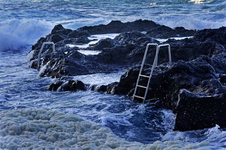 eruptive: Ocean waves and stairs in public pool of Termas da Ferraria, Sao Miguel island, Azores Stock Photo