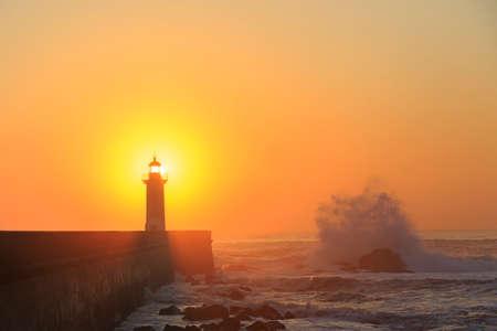 tormenta: Faro de Porto Felgueirasin con el chapoteo de la onda al atardecer, Oporto, Portugal