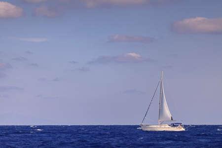 bateau de course: Bateau à voile avec grand-voile en mer bleu ouvert
