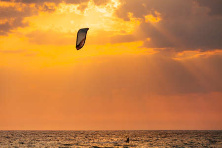 Kite surfer sailing in the sea at sunset ocean