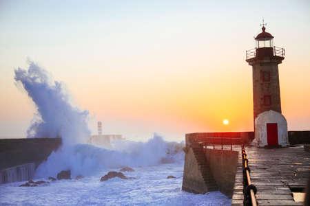 Lighthouse Felgueirasin Porto with wave splash at sunset, Porto, Portugal Stockfoto