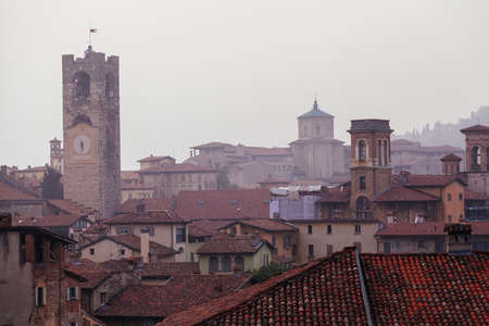 Bergamo bell tower and house roofs in fog Stockfoto