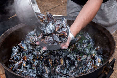 Chef with mussels in cauldron, blurred motion