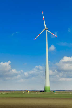 Rotating windmill blades in cloudy blue sky Stockfoto
