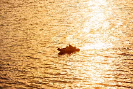 Motor dinghy sailing the sea at sunset with sun reflections on water