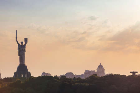 Motherland monument with sword and shield in Kyiv, Ukraine at sunset and city skyline