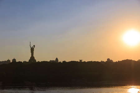 Motherland monument with sword and shield in Kyiv, Ukraine at sunset with sun