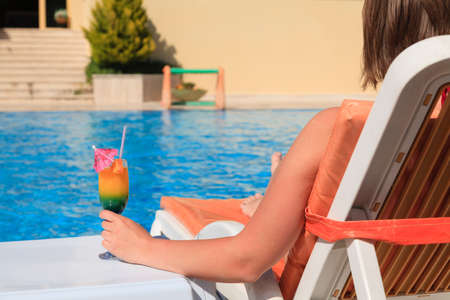 Woman hand with cocktail glass near swimming pool Stockfoto