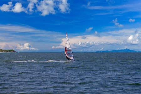 windsurf: Windsurfista en la navegación traje en el océano, azul cielo nublado Foto de archivo