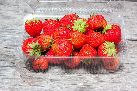 casings: Fresh strawberries in plastic box on a background of a wooden table Stock Photo