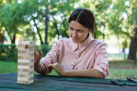 concentrates: Concentrates girl is playing in a wooden block game in the park