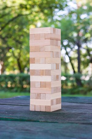 game block: Wooden game block standing on the table against the background blur park