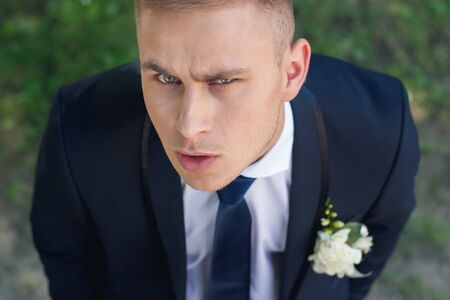 frowning: Frowning groom looks into the camera with your head on a green background Stock Photo