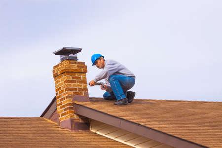 Costruttore dell'appaltatore con l'elmetto protettivo blu sul camino del calafataggio del tetto Archivio Fotografico