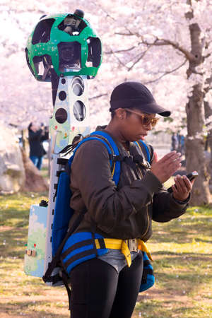Washington DC – April 3, 2019: Google Street View camera operator at work during the cherry blossom festival in Washington DC. It's a technology featured in Google Maps and Google Earth that provides panoramic views from positions along streets in the w
