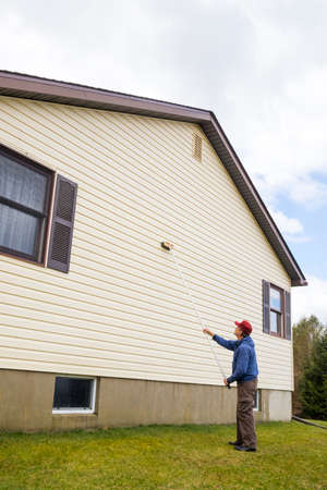 Homeowner washing mold from vinyl siding on north side of house with brush and cleaning fluid