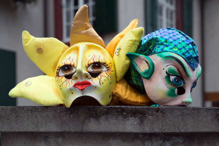 fasnacht: Two basel carnival masks resting on top of a garden wall, waiting for their owners.