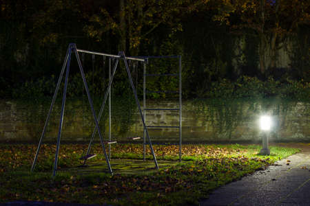 An empty playground with a metal swing at night with creepy atmosphere Stock Photo